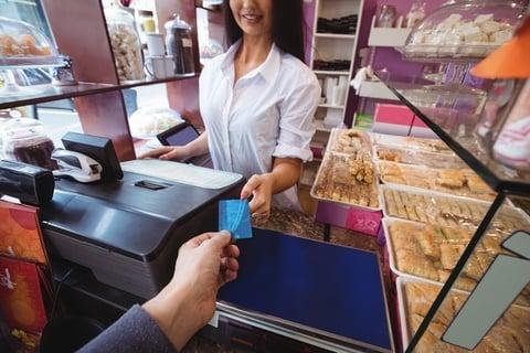 persona entregando tarjeta para realizar una compra en un local de postres