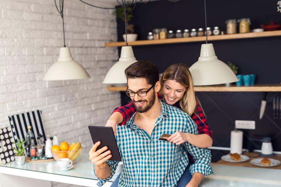 Esposa abraza a su esposo mostrando una tarjeta para realizar una compra a través de una tablet en una tienda digital